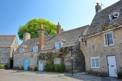 En rad av medeltida hus med brickstone- och stenhälltak i Corfe rockerar byn Royaltyfri Fotografi