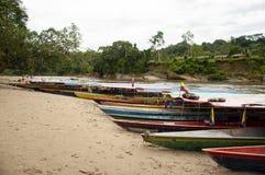 En rad av motoriserade kanoter som sitter på kanten av en flod royaltyfria bilder