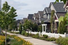 En rad av nya hem med en bred gångbana och posteringstaket Arkivfoton