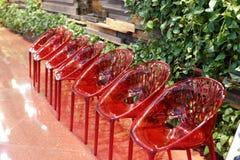 En rad av röda plast- stolar Fotografering för Bildbyråer