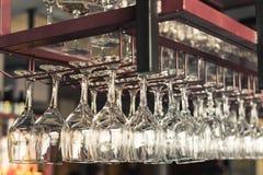 En rad av rena tomma vinexponeringsglas hänger Arkivfoto