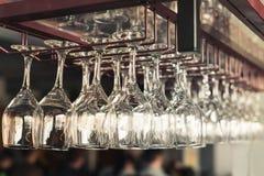 En rad av rena tomma vinexponeringsglas hänger Royaltyfri Fotografi