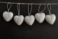 En rad av silverhjärtor som hänger på ett rep Royaltyfria Bilder
