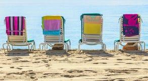 En rad av tre strandstolar Arkivbild