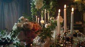 En rad av vinexponeringsglas och stearinljushållare på en tabell som tjänas som med svarta plattor, ljusstakar med stearinljus oc