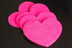 En rad från rosa hjärtor mot en mörk bakgrund Royaltyfria Foton