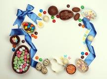 En ram av chokladeaster ägg, sötsaker av band och pilbågar på en isolerad vit bakgrund arkivbilder