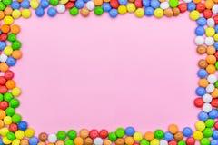 En ram av färgrika choklader Närbildsikt av överkanten, rosa bakgrund royaltyfri foto