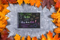 En ram av gula och orange höstlönnlöv på grå mörkerbetong Svart platta med kulör text Inskriften är hälsningau Arkivfoton