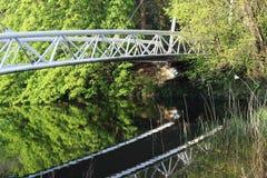 En reflexion av en vit bro i vatten bland gröna buskar och träd Royaltyfri Bild