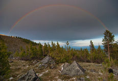 En regnbåge i bergen royaltyfri foto