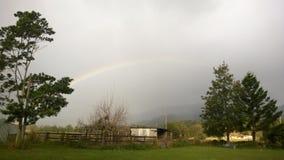 En regnbåge i molnen Arkivfoto