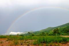 En regnbåge som uppstod efter regn, som uppstår på skogen på berget arkivfoton