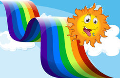 En regnbåge bredvid den lyckliga solen Arkivbild