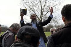 En religiös högtalare på högtalare tränga någon med utbredda armar Royaltyfri Foto