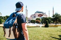 En resande man med en ryggsäck i den Sultanahmet fyrkanten nära den berömda Aya Sofia moskén i Istanbul i Turkiet Resor Fotografering för Bildbyråer