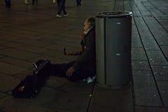 En resande musiker lutar tillbaka till en soptunna i det Milanese et Royaltyfri Foto