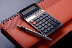 En reservoarpenna, en räknemaskin- och checkbok eller en anmärkningsbok arkivfoto