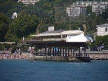 En restaurang i form av en segelbåt på pir nära stranden med många holidaymakers Yalta Crimea arkivbild