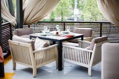 En restaurang med beautifully möblerade inre, bekväma fåtöljer och tjänade som tabeller på en rymlig utomhus- terrass Royaltyfri Bild