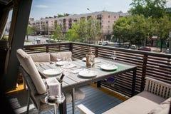 En restaurang med beautifully möblerade inre, bekväma fåtöljer och tjänade som tabeller på en rymlig utomhus- terrass Fotografering för Bildbyråer