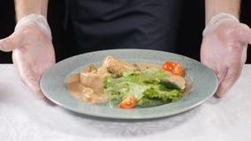 En restaurantvoedsel die koken dienen Chef-kok die in handschoenen schotel met kammosselen en verse mengeling van sla en arugula  stock videobeelden