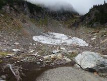 En rester snowfield i en dal Arkivfoto