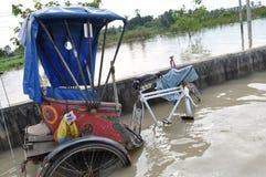 En rickshaw lämnas över på en översvämmad bro i Pathum Thani, Thailand, i Oktober 2011 Royaltyfri Fotografi