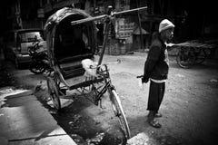 En Rickshawchaufför på gatorna av Katmandu, Nepal i svartvitt Royaltyfri Bild