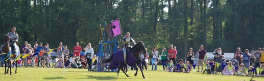 En riddare galopperar över fältet på en häst på densöder renässans Faire Royaltyfri Fotografi
