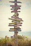 Riktnings underteckna postar på stranden Arkivbild