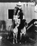 En ritt för två hästkraft, cowboy som rider två ponnyer (alla visade personer inte är längre uppehälle, och inget gods finns Leve Fotografering för Bildbyråer