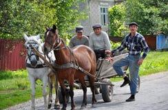 En ritt på en gata bär ett par av hästar och folk Arkivbilder