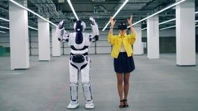 En robot kopierar kvinnans förehavanden, medan hon bär VR-exponeringsglas stock video