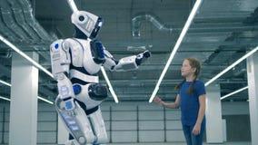 En robot och en flicka som trycker på händer, sidosikt Skolaunge, utbildning, vetenskapsgruppbegrepp arkivfilmer
