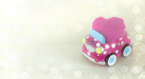 En rolig barns leksakbil som bär en rosa hjärtakudde Valentin begrepp för dagberöm bakgrundsbokehmusik bemärker tematiskt Royaltyfri Fotografi