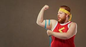 En rolig fet man i sportkläder mäter hans arm med en centim Royaltyfri Foto