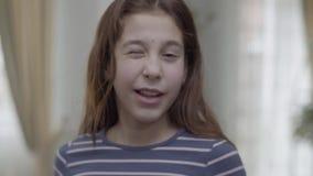 En rolig flicka att rymma orange baloon med emoji och framställning av samma emojiframsida med blinkningemoticonen stock video