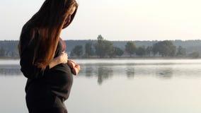 En rolig gravid kvinna spelar med behandla som ett barn häftklammermatare för ` s på solnedgången lager videofilmer