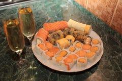 En romantisk matställe, champagneexponeringsglas och sushi Arkivfoton