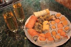 En romantisk matställe, champagneexponeringsglas och sushi Arkivbilder