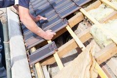 En roofer som lägger tegelplattan på taket Arkivfoto