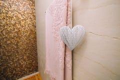 En rosa handduk torkas i badrummet på den upphettade handdukstången Arkivfoton