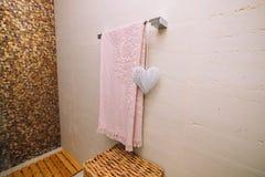 En rosa handduk torkas i badrummet på den upphettade handdukstången Arkivbild
