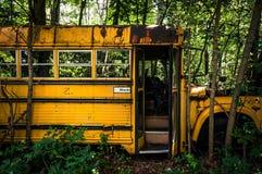 En rostig gammal skolbuss i en skrot royaltyfri foto