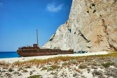 En rostig skeppsbrott på en stenig strand Royaltyfri Bild