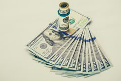 En rullad ihop räkning för dollar 100, som vilar på andra, metade räkningen för dollar som 100 isolerades på vit bakgrund Arkivbilder