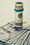 En rullad ihop räkning för dollar 100, som vilar på andra, metade räkningen för dollar som 100 isolerades på vit bakgrund Arkivfoto