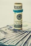En rullad ihop räkning för dollar 100, som vilar på andra, metade räkningen för dollar som 100 isolerades på vit bakgrund Royaltyfri Fotografi
