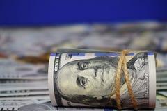 En rulle av dollar mot en bakgrund av spritt hundra dollarräkningar royaltyfri fotografi